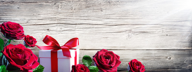 Gift Box And Roses On Vintage Wooden Background