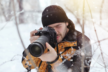 The young man, a photographer takes pictures on the camera in the winter sunny day on a blurred background at the forest,