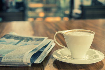 Cup of cappuccino with newspaper on the table in in the morning at coffee shop , warm tone