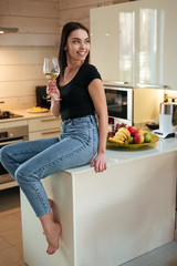 Vertical image of smiling woman sitting on kitchen