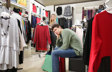 Man waiting his girlfriend while she choosing clothes in modern shop