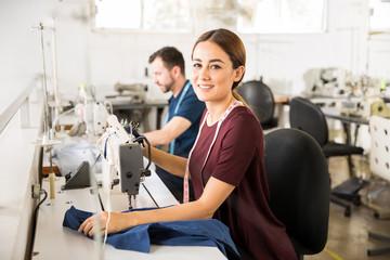 Pretty seamstress using a sewing machine