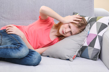 Cute girl suffering from headache while lying on sofa at home
