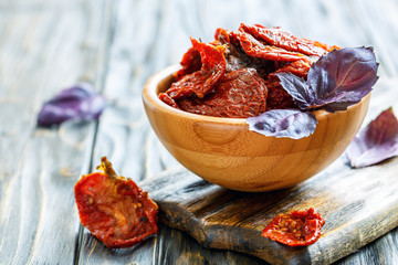 Sun-dried tomatoes and purple basil in a wooden bowl.