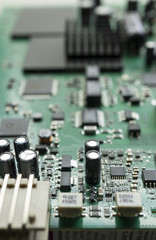 Detail of an electronic printed circuit board with many electrical components with swallow depth of field.
