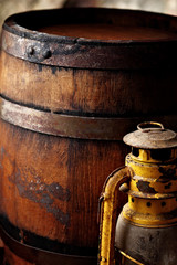 Old fashioned light kerosene lantern style oil lamp and barrels.closeup