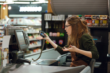 Confused cashier woman on workspace in supermarket