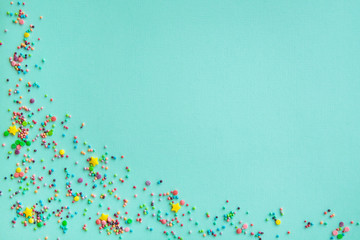 Easter background. Festive background. Multicolored powder on a turquoise background. Free space