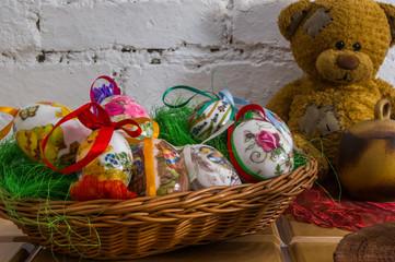 Wielkanocny świąteczny koszyk pisanek na tle białej cegły