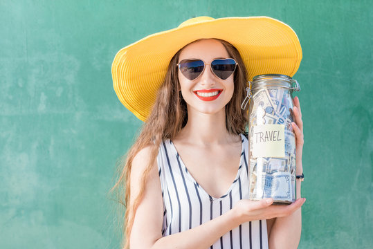 Young and happy woman in yellow hat holding a jar full of money for traveling on the green background. Money savings for summer vacation concept