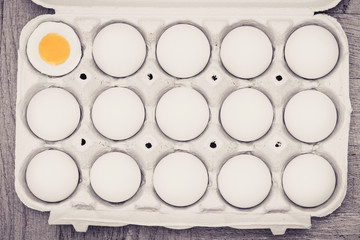 Eggs in a cardboard box, one is cracked open with a yellow yolk on a wooden background