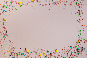 Easter background. Festive background. Multicolored powder on a beige background. Free space