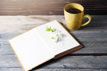 blank book cover on wood background with spring flower and cape of coffee