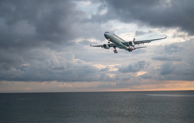 View from the beach on the landing airplane isolated above the sea over beautiful cloudy sky background
