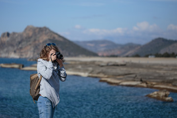 Young woman photographing rock ribbed Koru beach in Gazipasha