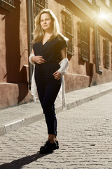 Beautiful blonde young woman walking on the street. Flare for text and design. Lifestyle girl in the city.