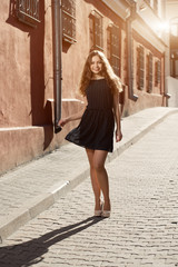 Beautiful brunette young woman wearing dress and walking on the street. Flare for text and design. Lifestyle in the city.