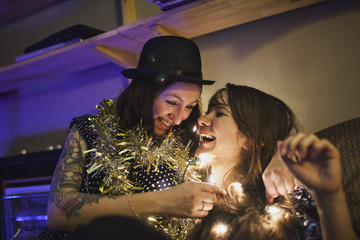 Two friends wrapped in tinsel and fairy lights