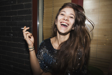 Laughing young woman smoking a cigarette