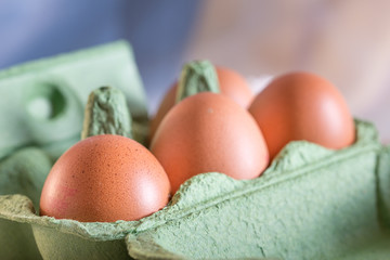 Four farm eggs in an egg box with a blue background.