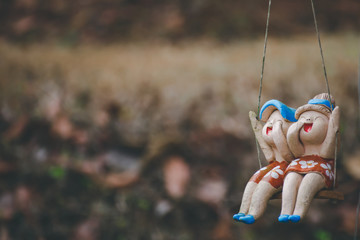 Clay child dolls sitting on swings in home, Concept of decoration and garden arrangement.