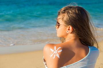 Sunbath protection. Woman using sun cream on the beach. Sun on a girl's shoulder, Sun-shaped cream on a young woman's skin,