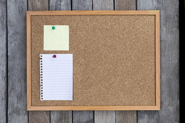 White memo pad and post-it on cork board over wood background