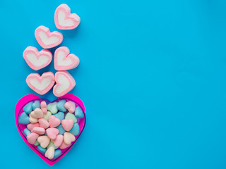 Marshmallow in a heart frame on Valentine's Day love concept on blue sky background