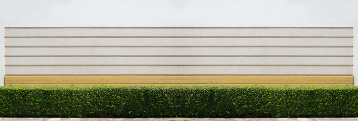 Concrete brick outdoor wall painted in white, ivory, light yellow colours with small green leaf bush as house fence for exterior design and decoration, big and wide background