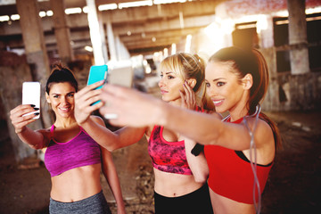 Group of fitness females taking selfies before training.