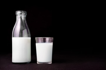 Bottle of milk  glass black background copy space