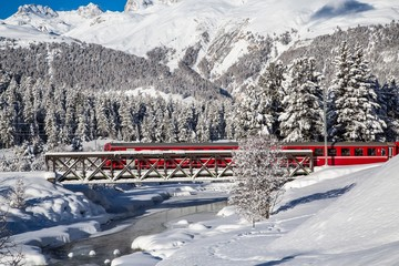 The red train of Bernina crosses a creek by a bridge. Engadine, Canton of Grisons, Switzerland Europe