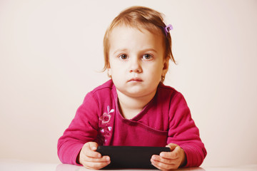 Little beautiful  girl with her smart phone (Development, education, technology)