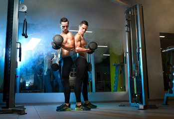 two men twin brothers training with dumbbells, exercising working out at the gym