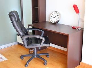 Workplace at home, business concept, desk and chair with clock and table lamp