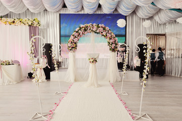 the beautiful wedding hall decorated with a decor in gentle white and powdery tones from compositions of fresh flowers