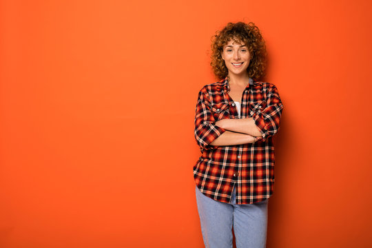 young natural curly woman standing over an orange background