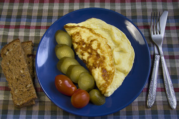 Omelette with vegetables on blue plate