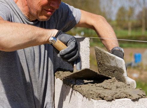 Etalement du ciment pour la construction d'un mur