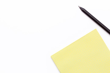 yellow notebook and black pencil on a white background. Minimal business concept.