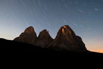 Startrail over the Sassolungo group in a moonless night in the Dolomites. Sella Pass. Fassa Valley. Trentino-Alto Adige. Italy. Europe