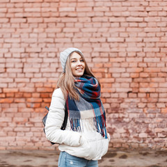 Cheerful beautiful young girl with a sweet smile in a white jacket and a colorful scarf with a black bag near the brick wall