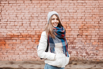 Young woman smiling in a white jacket and bright fashionable scarf near the wall