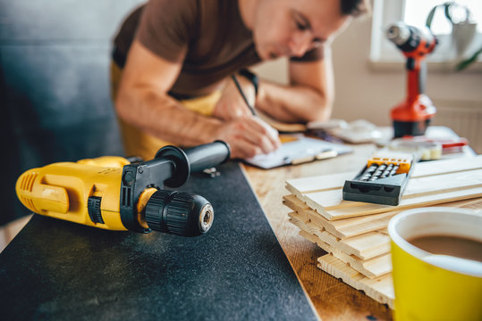 Power drill and Man making draft plan in the background
