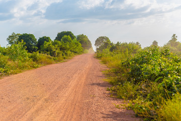 Empty dusty dirt road in rural Cambodia in Kampot province