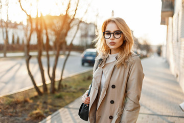 Beautiful young woman in stylish glasses and trendy coat with handbag in the day of spring at sunset