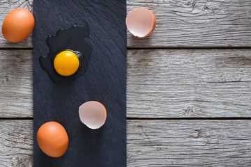 Brown organic cracked eggs with yolk on black wood background