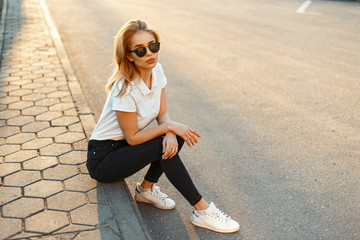 Beautiful stylish young blond girl in black glasses in a white polo shirt with black pants in white shoes sitting on the roadside at sunset