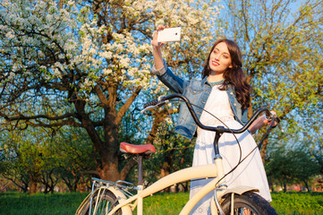 woman with bicycle taking selfie