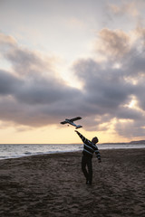 Man on a beach throwing the toy plane
